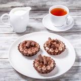 Wyśmienicie czekoladowe babeczki z filiżanką herbata i dzbanek mleko Zdjęcie Royalty Free
