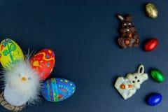 Wyśmienicie czekoladowi Easter jajka, królik i cukierki na zmroku, - błękitny tło fotografia royalty free