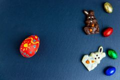 Wyśmienicie czekoladowi Easter jajka, królik i cukierki na zmroku, - błękitny tło obrazy stock