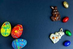 Wyśmienicie czekoladowi Easter jajka, królik i cukierki na zmroku, - błękitny tło obraz stock