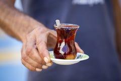 Wyśmienicie czerwona Turecka herbata z tradycyjna bonkreta kształtującym szkłem z teaspoon w mężczyzna ręce Zdjęcia Stock