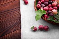 Wyśmienicie czerwoni agresty w jasnobrązowym koszu Healthful jagody na ciemnego brązu stole Fotografia Stock
