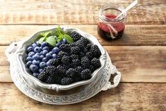 Wyśmienicie dojrzałe czarne jagody w pucharze i czernicy Obraz Royalty Free