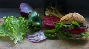Wyśmienicie domowej roboty hamburger, smażyć grule, świezi pomidory, sałata, cebule na nieociosanym drewnianym stole Fast food, n obrazy royalty free