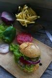 Wyśmienicie domowej roboty hamburger, smażyć grule, świezi pomidory, sałata, cebule na nieociosanym drewnianym stole Fast food, n zdjęcie stock