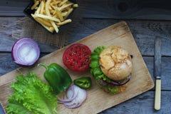 Wyśmienicie domowej roboty hamburger, smażyć grule, świezi pomidory, sałata, cebule na nieociosanym drewnianym stole Fast food, n zdjęcie royalty free