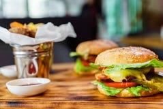Wyśmienicie domowej roboty hamburgery z soczystym cielęciny cutlet na drewnianym stole Fotografia Stock