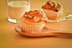Wyśmienicie domowej roboty migdałowi muffins i szkło mleko na drewnianym zdjęcie royalty free