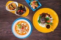 Wyśmienicie Foods na drewno stole, jedzenie na kolorowych naczyniach fotografia royalty free