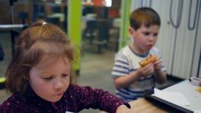 Wyśmienicie francuz i hamburger smażymy z kumberlandem dla małej dziewczynki i chłopiec, zabawa żartuje sztukę z posiłkiem w fast zbiory wideo