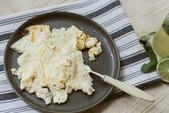 Wyśmienicie gotujący omlet na szarym pieluchy i beżu dywanie Domowej roboty lemoniada i rozdrapani jajka dla śniadaniowych Ciemny obrazy royalty free