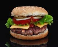 Wyśmienicie hamburger z wołowiną z serem, pomidory, cebule, ogórki, pomidory i ketchup, na czarnym tle i na bla Obraz Royalty Free
