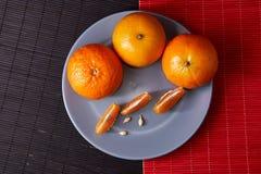 Wyśmienicie i Piękni Tangerines Obrana Tangerine pomarańcze i Tangerine pomarańczowi plasterki na Ciemnym tle tła cytrus przygoto Zdjęcie Royalty Free