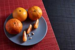 Wyśmienicie i Piękni Tangerines Obrana Tangerine pomarańcze i Tangerine pomarańczowi plasterki na Ciemnym tle tła cytrus przygoto Obrazy Royalty Free