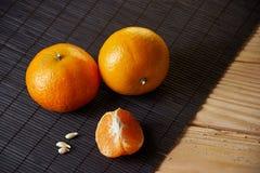 Wyśmienicie i Piękni Tangerines Obrana Tangerine pomarańcze i Tangerine pomarańczowi plasterki na Ciemnym tle tła cytrus przygoto Zdjęcia Royalty Free