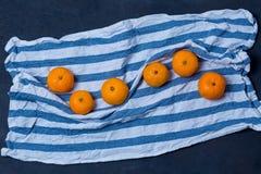 Wyśmienicie jaskrawego soczystego mandarynka mandarynu kuchennego ręcznika tkaniny błękitny biały pasiasty płótno na zmroku - błę fotografia stock