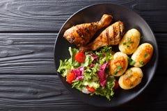 Wyśmienicie jedzenie: piec na grillu kurczaków drumsticks z nowymi grulami i obrazy stock