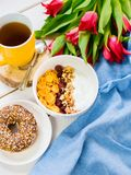 Wyśmienicie jogurtu puchar z kukurydzanymi płatkami, dokrętkami i dżemem na białym drewnianym stole, Zdrowy i organicznie odżywia zdjęcie stock