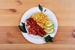 Wyśmienicie kiełbasy z warzywami na drewnianym tle Zdjęcia Stock