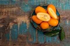 Wyśmienicie mali cytrus owoc kumquats zamknięci up na drewnianym stole Obrazy Royalty Free