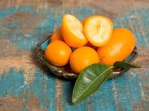 Wyśmienicie mali cytrus owoc kumquats zamknięci up na drewnianym stole Zdjęcie Royalty Free