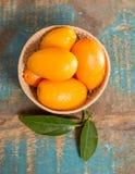Wyśmienicie mali cytrus owoc kumquats zamknięci up na drewnianym stole Obraz Stock