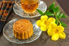 Wyśmienicie mooncake i gorąca herbata z kwiatu żółtymi elementami Obrazy Royalty Free