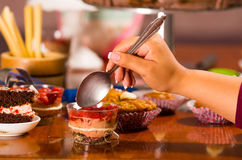 Wyśmienicie mousse zakrywający w truskawkowej polewie, przedstawiający inside mali szkła, ręki mienia chwytać łyżkowy kąsek, tort Fotografia Stock