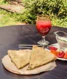 Wyśmienicie nieociosany crispy kulebiak z serem i ziele Słuzyć na drewnianym talerzu, otaczającym szkłem pomidorowy sok, biały ku Zdjęcie Stock