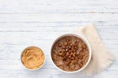 Wyśmienicie oatmeal w białym pucharze, dat owoc i kakao, zdrowy śniadanie na bławym tle zdjęcia royalty free