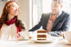 Wyśmienicie płatowaty tort słuzyć z kawą na stole młoda para obrazy stock