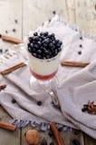 Wyśmienicie parfait deser z borówką, dojnym souffle i jello warstwami, Zamarznięta funda w szkle na nieociosany drewnianym Zdjęcie Stock