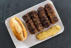 Wyśmienicie piec na grillu minced mięśni rolek mici ori mititei romanian i Balkan tradycyjnych naczyń słuzyć z musztardą i chlebe zdjęcia stock