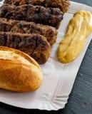 Wyśmienicie piec na grillu minced mięśni rolek mici ori mititei romanian i Balkan tradycyjnych naczyń słuzyć z musztardą i chlebe zdjęcie stock