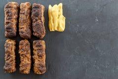 Wyśmienicie piec na grillu minced mięśni rolek mici ori mititei romanian i Balkan tradycyjnych naczyń słuzyć z musztardą na czarn zdjęcia stock