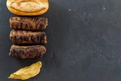 Wyśmienicie piec na grillu minced mięśni rolek mici ori mititei romanian i Balkan tradycyjnych naczyń słuzyć z musztardy i chleba fotografia stock