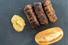 Wyśmienicie piec na grillu minced mięśni rolek mici ori mititei romanian i Balkan tradycyjnych naczyń słuzyć z musztardy i chleba zdjęcie royalty free