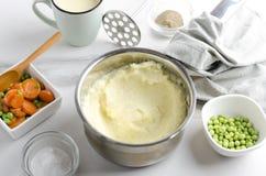 Wyśmienicie puree ziemniaczane w garnku, pucharach z różnymi pikantność, warzywach i filiżance mleko, Smakowity i zdrowy jedzenie zdjęcie stock