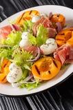Wyśmienicie romantyczna sałatka z mozzarellą, baleronem, moreli sałatą w górę talerza, piec na grillu dalej i świeżą pionowo zdjęcie stock
