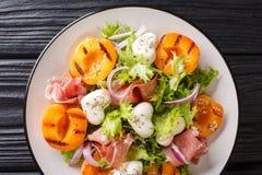 Wyśmienicie romantyczna sałatka z mozzarellą, baleronem, moreli sałatą w górę talerza, piec na grillu dalej i świeżą horyzontalny obraz stock