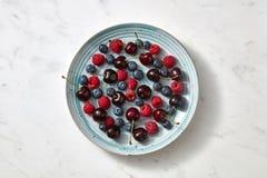 Wyśmienicie słodka wiśnia, czarna jagoda, malinka na błękitnym talerzu na szarym marmurowym tle z kopii przestrzenią zdjęcie stock