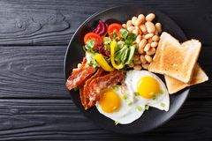 Wyśmienicie smażący jajka, bekon, fasole, grzanka i świeży warzywo sa, zdjęcie royalty free