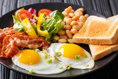 Wyśmienicie smażący jajka, bekon, fasole, grzanka i świeży warzywo sa, obraz royalty free