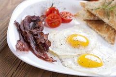 Wyśmienicie smażący jajko z pikantność, bekonem, croutons i pomidorami, dalej zdjęcie stock