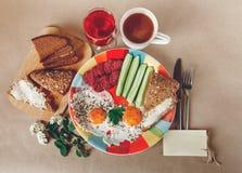 Wyśmienicie Smakowity śniadanie od jajek, chleb z masłem, kiełbasa na Colorfull talerzu Kawa, Czerwony sok z Białymi kwiatami Życ Obrazy Royalty Free