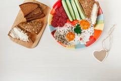 Wyśmienicie Smakowity śniadanie od jajek, chleb z masłem, kiełbasa na Colorfull talerzu Życzenia serca karta Biały tło Obraz Royalty Free