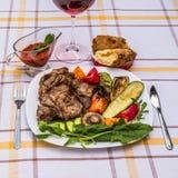Wyśmienicie soczyści piec na grillu stek, warzywa i pieczarki na talerzu, otaczającym pomidorami, świeżymi ziele i czerwonym gril Zdjęcia Royalty Free