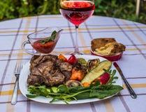 Wyśmienicie soczyści piec na grillu stek, warzywa i pieczarki na talerzu, otaczającym pomidorami, świeżymi ziele i czerwonym gril Fotografia Royalty Free