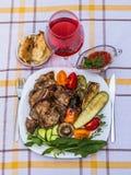 Wyśmienicie soczyści piec na grillu stek, warzywa i pieczarki na talerzu, otaczającym pomidorami, świeżymi ziele i czerwonym gril fotografia stock