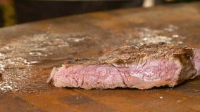 Wyśmienicie, soczysty, świeżo gotujący mięsny stku kucharz, ciie kawałki i usuwa od tnącej deski Sok od stków zbiory